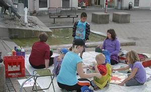 Kinder mit Malsachen auf einem Platz