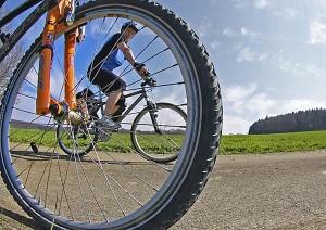 Blick durch Fahrrad mit Speichen auf Radfahrerin
