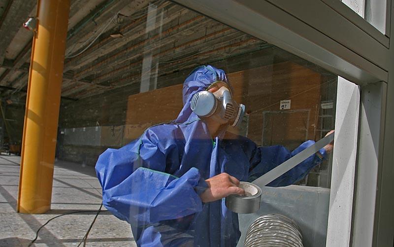 Arbeiter in Schutzanzug mitz Atemschutzmaske beim Abkleben