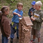 Kinder stehen um Turm aus Holzteilen