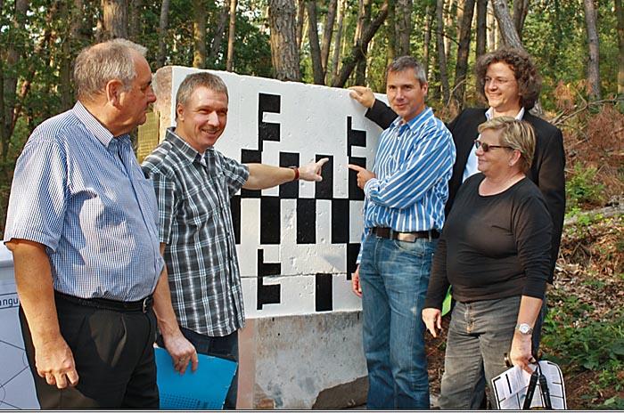 Menschengruppe vor Stein mit schwarz-weißem Muster