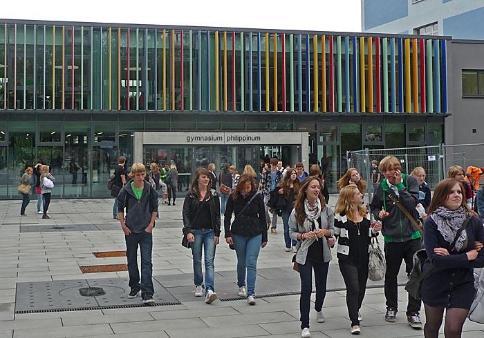 Paushof mit Schülern dahinter bunte Fassade von Anbau