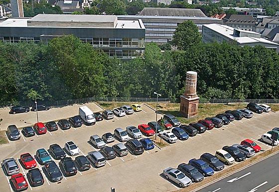 Blick vom Parkhaus Pilgrimstein auf den jetzigen Pakrplatz auf dem vormaligen Gelände der Marburger Baurerei, an die alleine noch der Schornsteinstummel erinnert. Hinter dem Mühlgraben Hörsaalgebäude und Uni-verwaltungsgebäude. Foto Hartwig Bambey