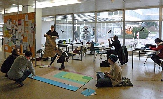 Eine Arbeitsgruppe Studierender der Erziehungswissenschaf:Lesen und schreiben am Notebook, Farbblätter auswählen, sortieren und strukturieren und montieren einer Präsentation werden als Gruppenprozess werden im Sitzen, Hocken und Stehen vollzogen. Das Foyer der Philosophischen Fakultät zwischen der Türmen nahe der Universitätsbibliothek bietet Raum und Umgebung dafür. Foto Hartwig Bambey