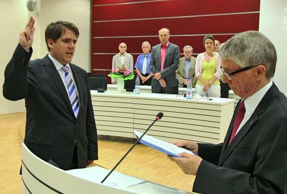 Kreistgsvorsitzender Detlev Ruffert , rechts, vereidigt den neue gewählten Ersten Kreisbeigeordneten Marain Zachow (CDU).  Im Hintergrund in der Mitte der zuvor abgewählte bisherige Erste Kreisbeigeordnete Karsten McGovern und rechts Landrätin Kirsten Fründt.