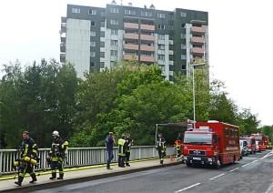 Erschöpfte Feuerwehrleute nach stundenlagem Einsatz, im Hintergrund das Hochaus, in dessen Keller am 25. Juni 2014ein Feuer ausgebrochen war. Sternbald-Foto Hartwig Bambey