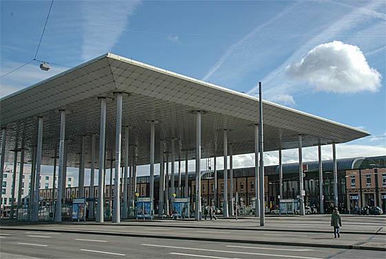 Das riesige Dach über dem Bahnhofsvorplat is Erkenungszeichen des Bahnhofs Kassel-Wilhelmshöhe. Seine Besonderheit und statisches Charakteristikum sind die unerschiedlichen Abstände zwischen den Tragstützen. Foto Wikipedia cc.