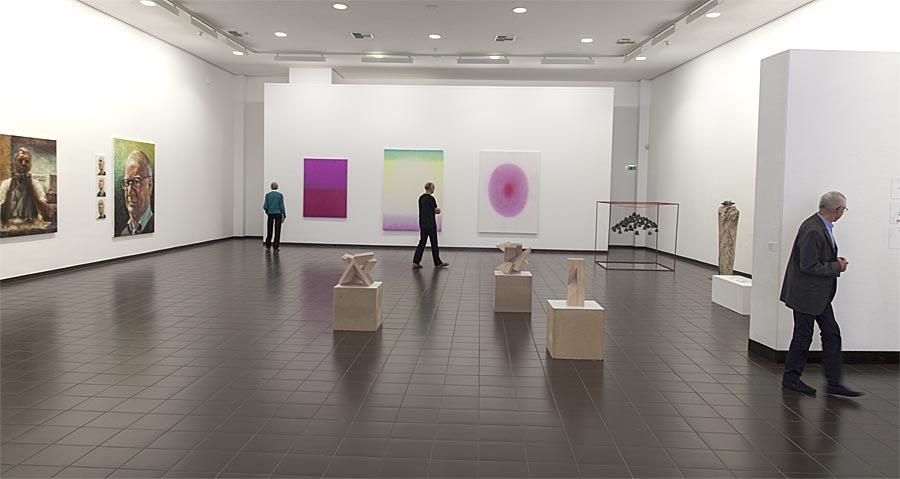 Im oberen Saal dominieren und imponieren Rainer Lather´s Gemälde als großformatige klassich gemalte Portraits und kontrastierend dazu die farbinspirierte und formlos-abstrakten Malerei von Christine Dahrendorf an der Stirnwand. Sternbald-Foto Hartwig Bambey